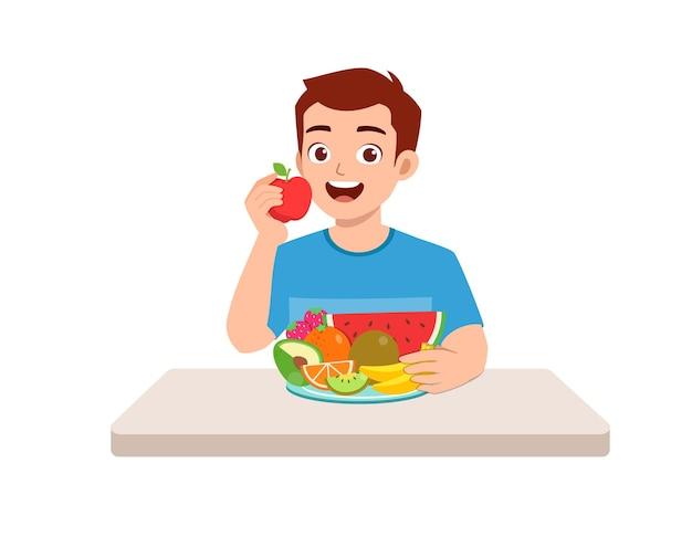Le jeune homme beau mange des fruits et des légumes