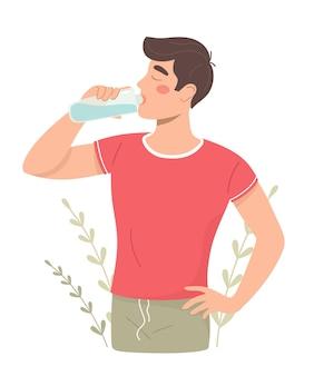 Un jeune homme boit de l'eau d'une bouteille