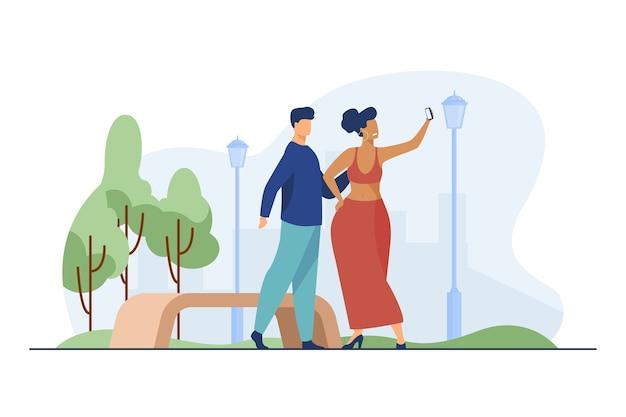 Jeune homme et femme prenant une photo dans le parc.