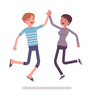 Jeune homme et femme sautant donnant haut cinq