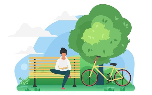Jeune homme lisant un livre dans un parc près du vélo