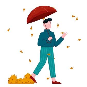 Jeune homme marchant avec un parapluie en automne