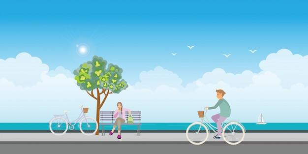 Jeune homme monté sur des vélos et jeune femme mangeant une glace.