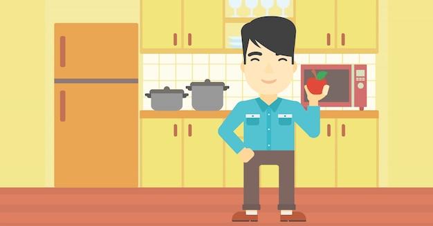 Jeune homme à la pomme dans la cuisine.