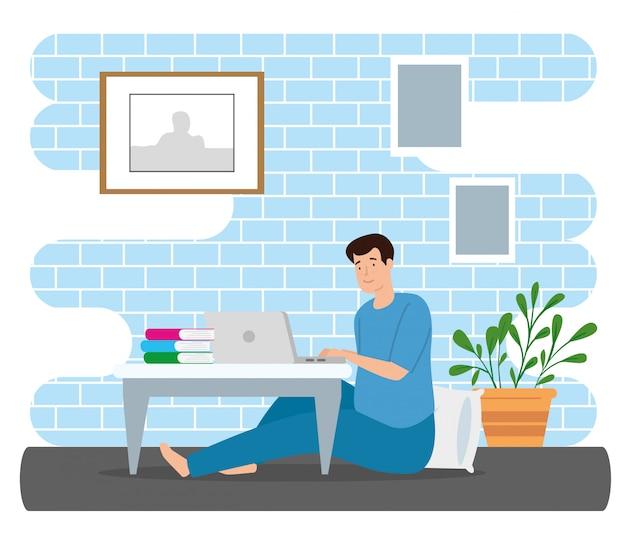 Jeune homme reste à la maison à l'aide d'un ordinateur portable