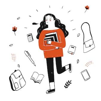 Jeune jolie étudiante tenant des livres marchant dans la rue