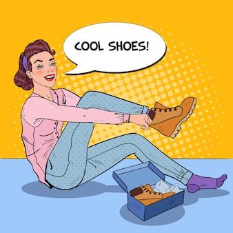 Jeune jolie femme essayant de nouvelles bottes