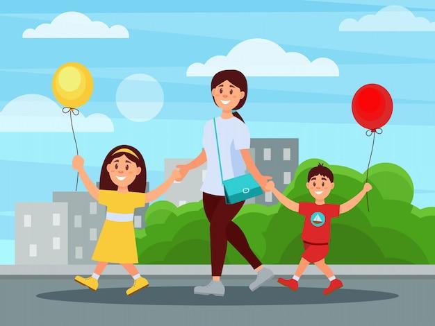 Jeune maman marche dans le parc avec ses enfants. bâtiments et buissons en arrière-plan. garçon et fille tenant des ballons dans les mains. journée familiale. enfance heureuse. appartement