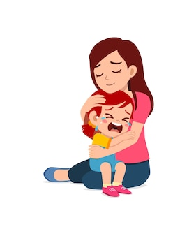 Une jeune mère embrasse une petite fille qui pleure et essaie de la réconforter