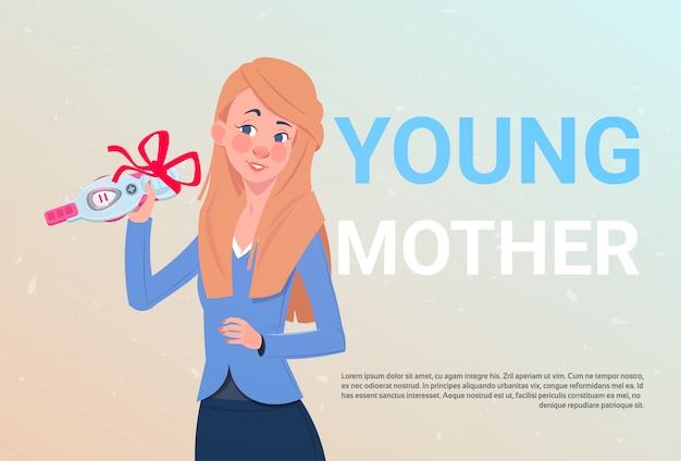 Jeune mère tenant un test de prénatie positif avec un noeud de ruban rouge sur un fond de modèle