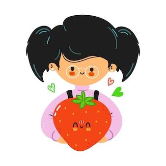 Jeune mignonne petite fille drôle tenir la fraise à la main