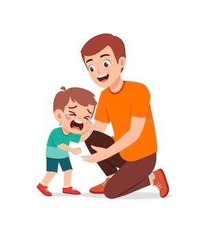 Le jeune père embrasse le petit garçon qui pleure et essaie de le réconforter