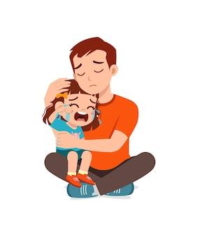 Le jeune père étreint la petite fille qui pleure et essaie de réconforter