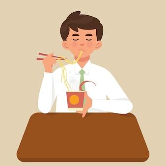 Jeune travailleur mange une tasse de nouilles instantanées pour le déjeuner