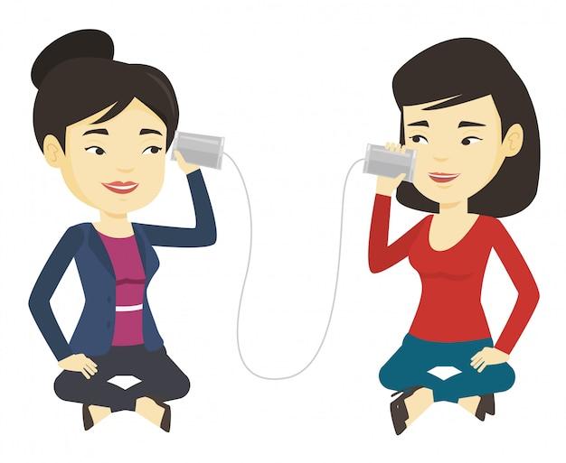 Jeunes amis parlant à travers un téléphone en étain
