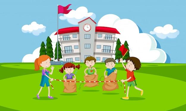 Jeunes enfants ayant une course de sac de pommes de terre