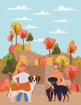 Jeunes hommes avec des mascottes de chiens mignons dans le camp d'automne
