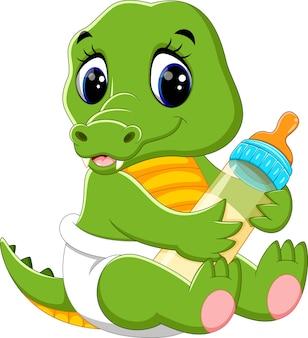 Joli bébé crocodile tenant une bouteille de lait