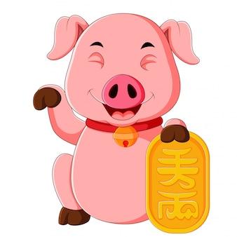 Un joli cochon rose tient les logos dorés du nouvel an chinois