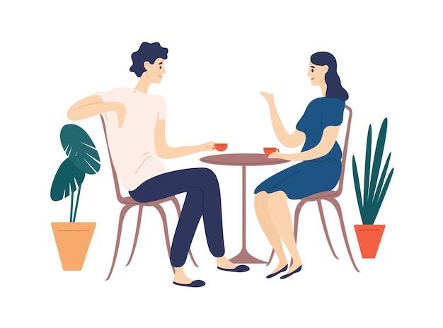 Joli couple assis à table, boire du thé ou du café et parler. jeune homme drôle et femme au café à la date