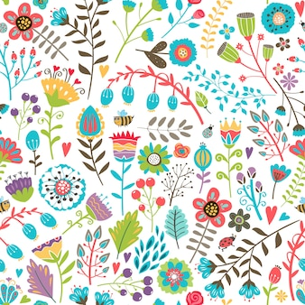 Joli modèle sans couture avec des fleurs d'été colorées dessinées à la main dispersées au hasard dans un design occupé adapté au papier et au tissu d'emballage de papier peint