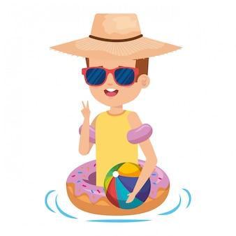 Joli petit garçon avec un flotteur de beignets et un ballon de plage