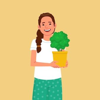 Jolie femme tient un pot avec une plante d'intérieur hobby pour faire pousser des plantes d'intérieur