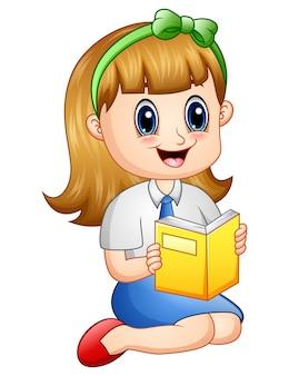 Jolie fille dans un uniforme scolaire, lisant un livre