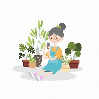 Jolie fille jardinage tenant illustration de livre pour enfants smartphone
