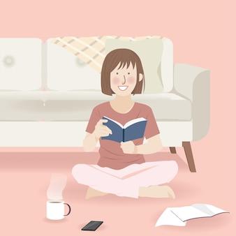 Jolie fille lisant un livre en pyjama dans le salon avec boisson
