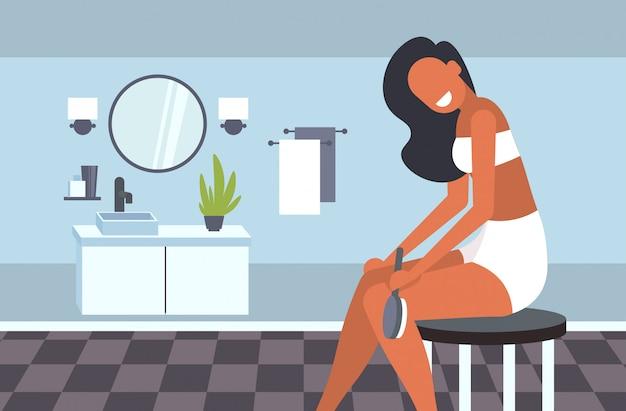 Jolie fille massant la peau de ses jambes avec une brosse pour massage sec traitement de la cellulite brossage à sec concept de soins de la peau salle de bain moderne intérieur illustration horizontale