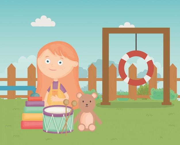 Jolie fille avec pyramide ours tambour dans le parc, jouets pour enfants
