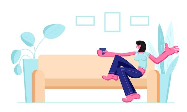 Jolie fille souriante assise sur un canapé confortable, boire du café ou du thé à la maison