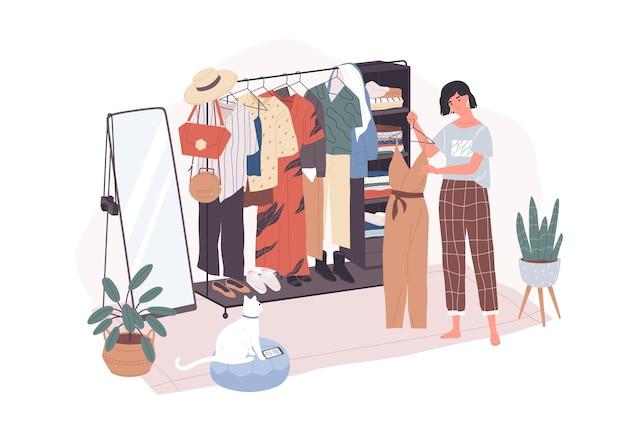 Jolie jeune femme debout devant un porte-cintres et essayant de choisir une tenue