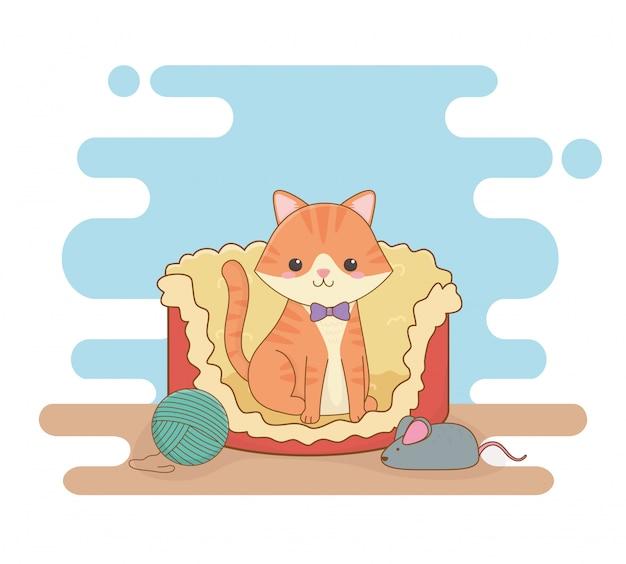Jolie mascotte de chat au lit avec rouleau de laine et souris