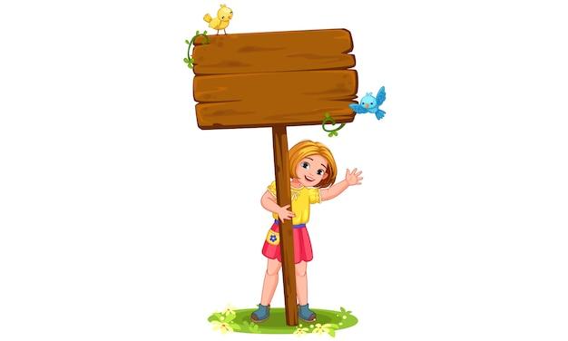Jolie petite fille derrière la planche de bois vierge