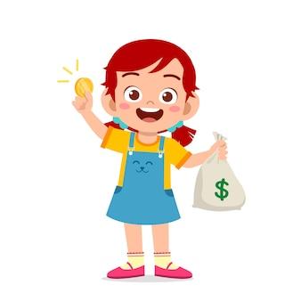 Jolie petite fille enfant portant un sac d'argent et de pièces de monnaie
