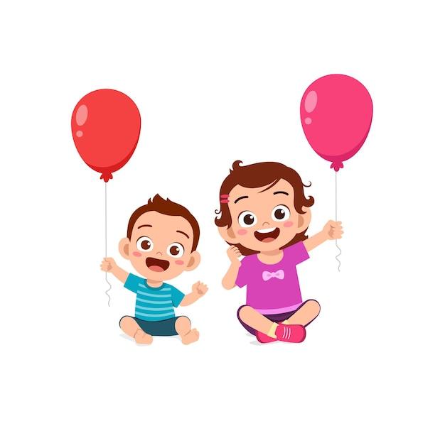 Jolie petite fille joue au ballon avec son petit frère