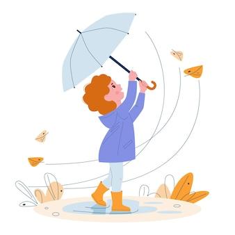 Jolie petite fille avec parapluie dans des bottes en caoutchouc feuilles d'automne par temps venteux