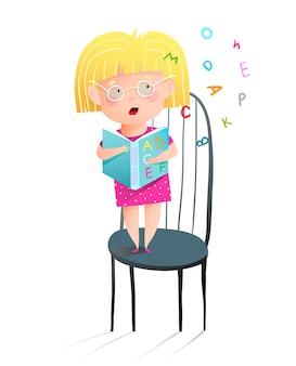 Jolie petite fille portant des lunettes en lisant le livre abc à haute voix debout sur une chaise