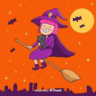 Jolie sorcière d'halloween sur un balai