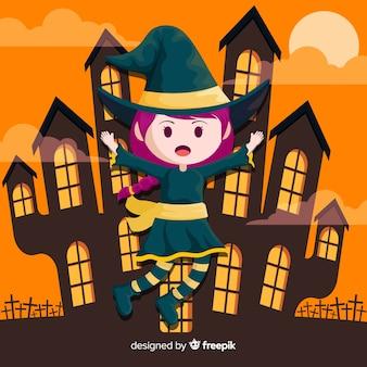 Jolie sorcière d'halloween avec la maison hantée