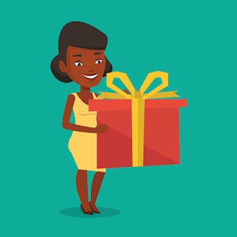 Joyeuse femme africaine tenant la boîte avec un cadeau.