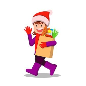 Joyeuse petite fille en vêtements d'hiver transportant des provisions