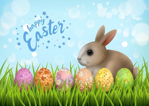 Joyeuses pâques carte avec de l'herbe, des oeufs peints et mignon petit lapin