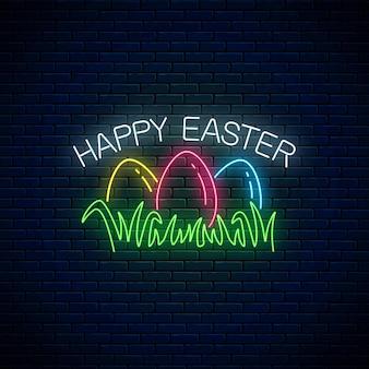 Joyeuses pâques enseigne lumineuse avec des oeufs colorés sur l'herbe dans un style néon sur fond de mur de brique sombre.