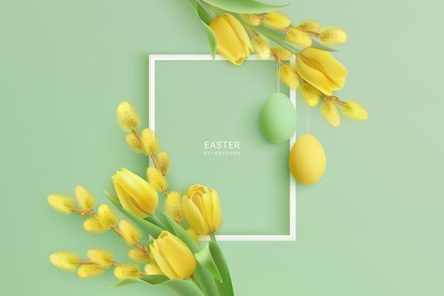 Joyeuses pâques avec des tulipes jaunes et des branches de saule avec des oeufs de pâques suspendus et cadre blanc