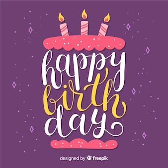 Joyeux anniversaire lettrage dessiné avec un gâteau à la main