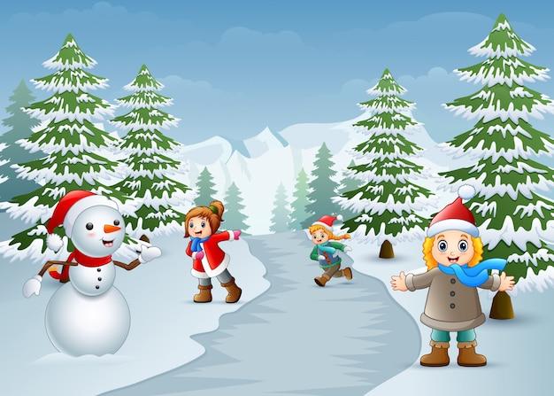 Joyeux enfants jouant avec un bonhomme de neige en hiver