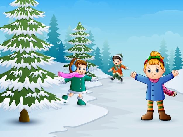 Joyeux enfants jouant dans le paysage d'hiver